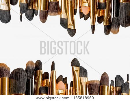 Frame of various makeup brushes isolated over white with copy space in the middle