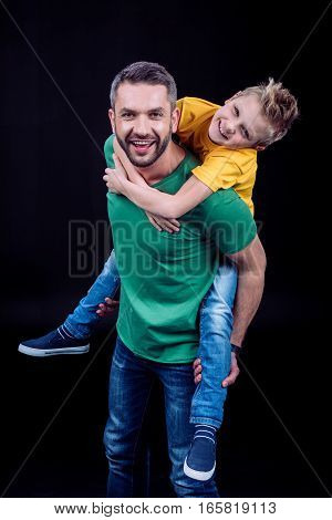 Smiling father piggybacking happy child and looking at camera