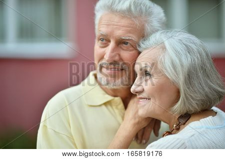 Close-up portrait of a smiling senior couple in summer park