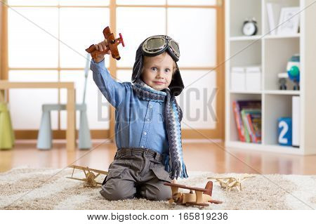 Child boy pretending to be aviator. Kid playing with toy airplanes at home. Travel and dream concept
