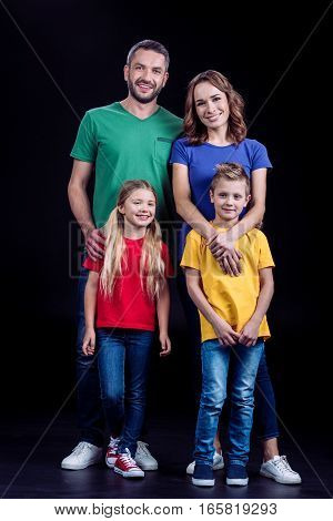 Happy family standing in colorful t-shirts and smiling at camera on black