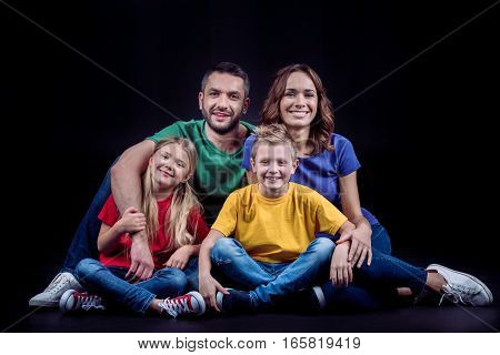 Happy family in colored t-shirts sitting together and looking at camera