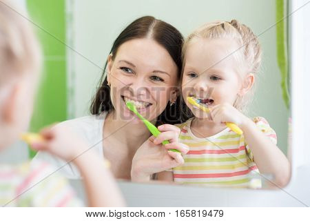 Mother And KId Daughter Brushing Teeth Together