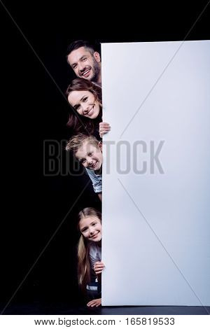 Happy family holding blank white card and looking at camera on black