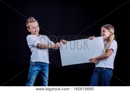 Smiling siblings standing with blank white card in hands on black