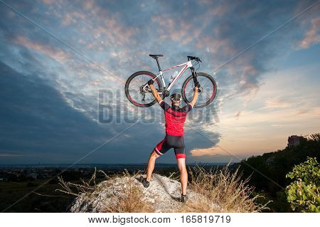 Cyclist Raising The Mountain Bike Above His Head With Success