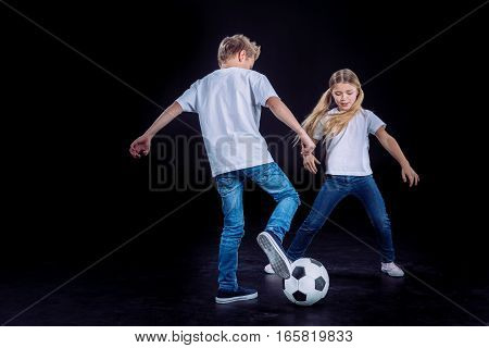 Happy brother and sister playing with soccer ball on black
