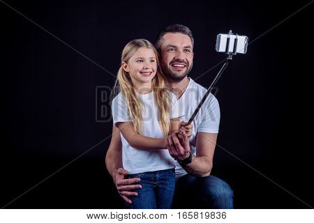 Happy father and daughter taking selfie together on black