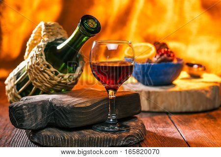 Red wine in the wineglass and bottle. Fruit in bowl over fireplace light