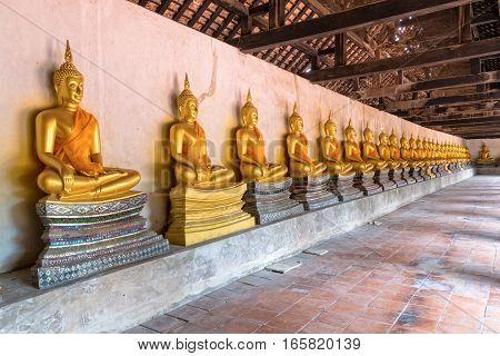 Row of golden buddha statue sitting at Wat Phutthaisawan temple in Ayutthaya Historical Park Phra Nakhon Si Ayutthaya Province Thailand