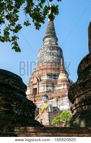 Buddha statue at the bottom of a large ancient pagoda on blue sky background at Wat Yai Chai Mongkon temple in Phra Nakhon Si Ayutthaya Historical Park Ayutthaya Province Thailand