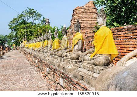 Row of Buddha statue sitting at Wat Yai Chaimongkol temple in Phra Nakhon Si Ayutthaya Historical Park Ayutthaya Province Thailand