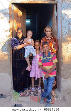 LUXOR, EGYPT - NOVEMBER 6, 2011: An Egyptian family posing at the entrance of her house in the village of Gabawi