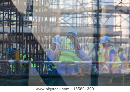 Construction site with team of construction laborers working on scaffold. Trough the glass shot. Window reflections can be seen in frame.
