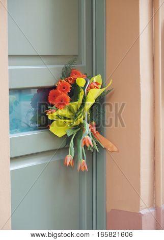 Green door with bouquet of paper flowers