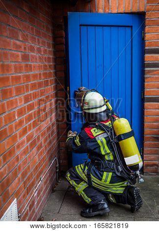 HDR - Firefighter in action before house door