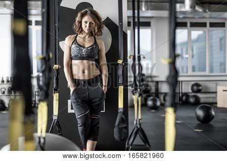 Charming sportive woman with curly hair stands on the floor in the gym on the background of the partition. She wears dark pants and top. Girl looks into the camera with a smile. Horizontal.