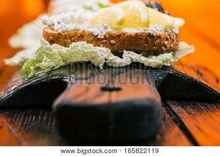 Sandwiches with farmer cheese and lemon. Serving on rustic wood