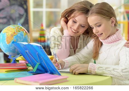 Portrait of young mother helps her daughter with homework