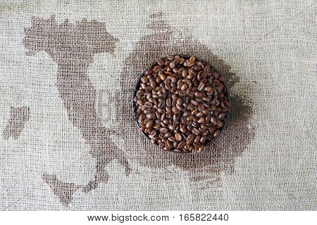 Burlap texture with coffee crop in a bowl background, plenty of robusta beans in plate. Sack cloth canvas with with Italy map spot in the middle. Heap of seeds at hessian textile