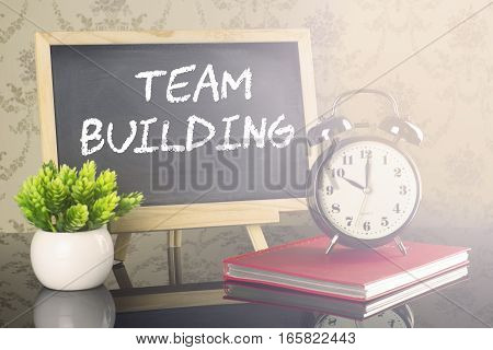Team Building on blackboard with clock and flare