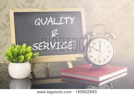 Quality And Service on blackboard with clock and flare