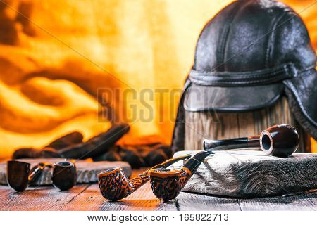 Various smoking pipes on wood boards. Winter gloves and hat over fire light background