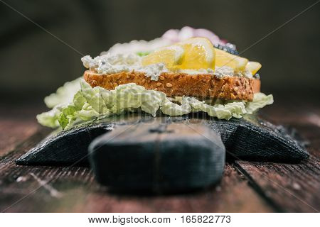 Sandwiches with white cheese and lemon served on rustic wood