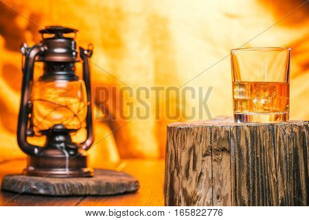 Glass of whiskey on wood stamp. Fire light background with vintage lamp