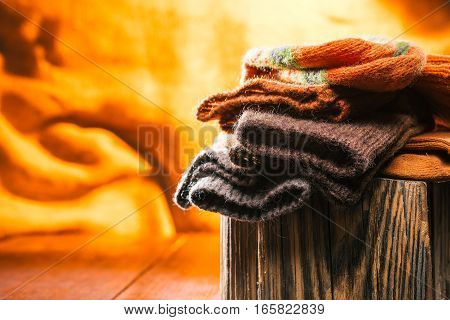 Handmade wool socks on wood stamp over fire background