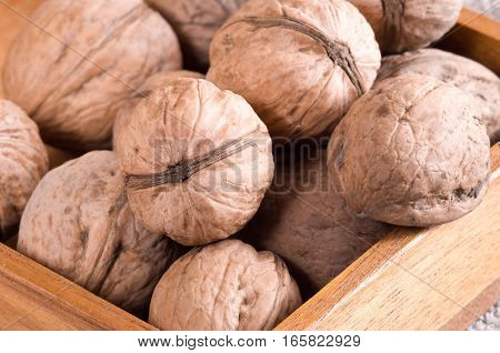 Macro View Of A Group Of Walnuts In A Brown Wooden Box