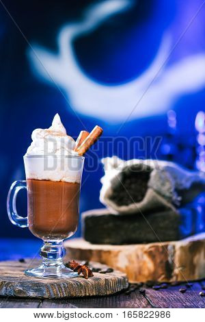 Glass of irish coffee and sack of coffeebeans in blue lighting