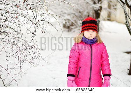 Upset Little Girl In Beautiful Winter Park During Snowfall