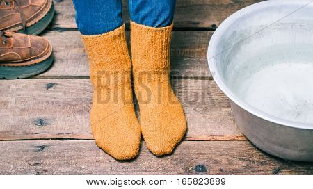 Feet wearing wool socks near basin with warm water on the floor before footbath. Color toning