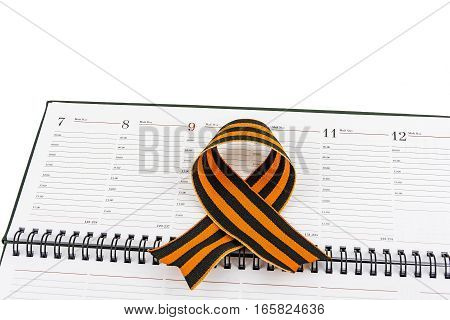 In an open diary sheet is St. George's ribbon in a bow