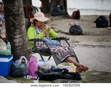 31 december 2016 otres beach sihanoukville cambodia young asian woman at the beach sitting in a chair using her smartphone editorial image
