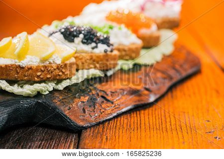 Sandwiches of bran bread with cottage cheese spread. Fire lighting background