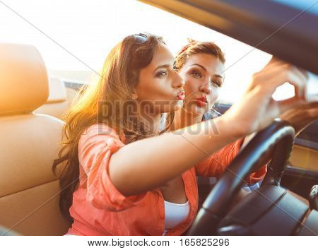 Two young beautiful girls are doing a photo of yourself in a convertible