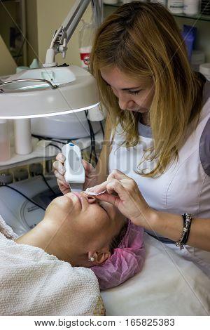 Woman getting face skin treatment. Facial skin peeling in beauty salon.