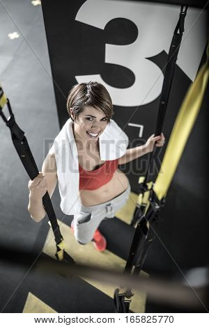 Pretty smiling girl stands in the gym next to black partition and holds TRX straps. She wears red top and sneakers, gray pants and has a white towel. Girl looks into the camera. Vertical.