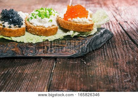 Toasts with farmer cheese, caviar and green onion served on wood board