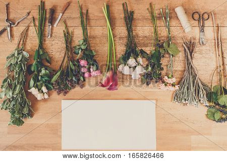 Flower shop delivery background. Empty white paper sheet with copy space and fresh flowers bouquets and blackberries on wood, top view. Roses and coral callas
