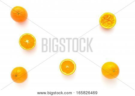 Closeup of whole halved and squeezed oranges on white as food background with lots of copy space.
