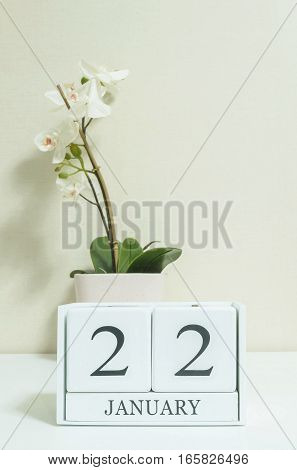 Closeup white wooden calendar with black 22 january word with white orchid flower on white wood desk and cream color wallpaper in room textured background selective focus at the calendar