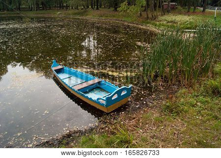Wooden Boat, fall on a pond in a city Park