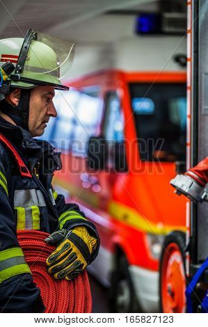 HDR - Fireman in action with a rolled fire hose on the emergency vehicle