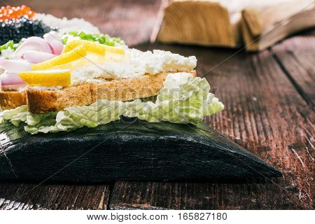 Sandwiches with fresh cheese spread and tops of lemon, caviar and onions on natural wood board