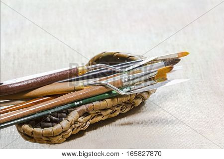 Brushes and palette knifes in a wicker bast on a gray canvas