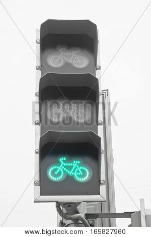 green traffic light for bicyclists on background of the sky