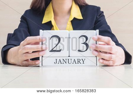 Closeup white wooden calendar with black 23 january word in blurred working woman hand on wood desk in office room selective focus at the calendar